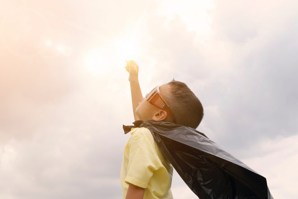 boy in superhero cape with arm to sun and sky