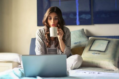 woman sipping coffee on bed with laptop