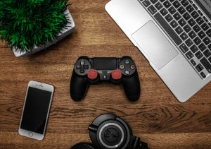Topshot of laptop, cell phone, camera & game system controller.