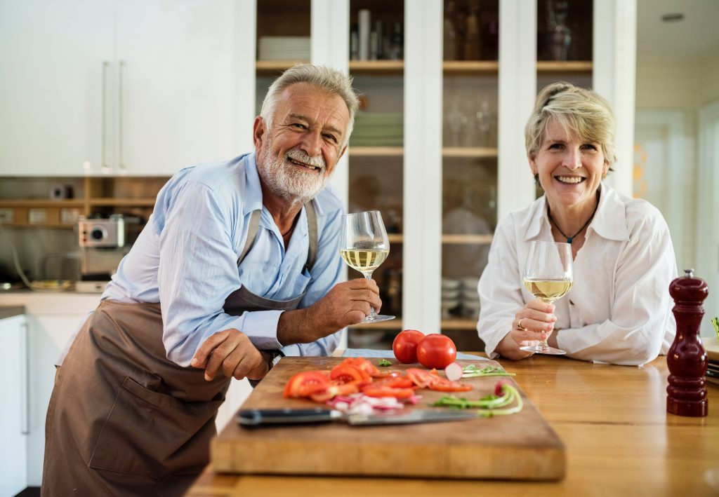 Elderly couple drinking wine at a kitchen island.