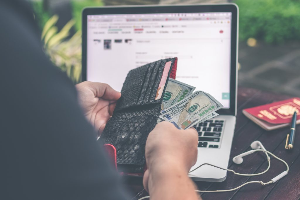 man taking money from his wallet at computer